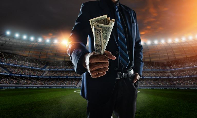 Man in suit holding a wad of cash in a football stadium with bright lights shining in the background