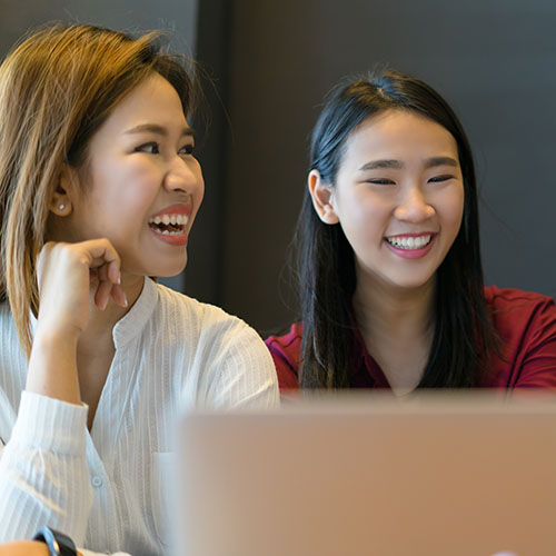 two-Asian-female-students-smiling-and-looking-at-screen