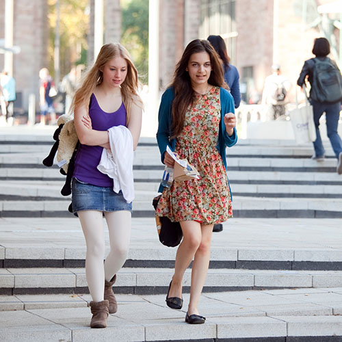 two-female-students-walking-outside-the-hub